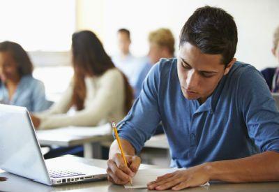 Gutt sitter og studerer ved pulten