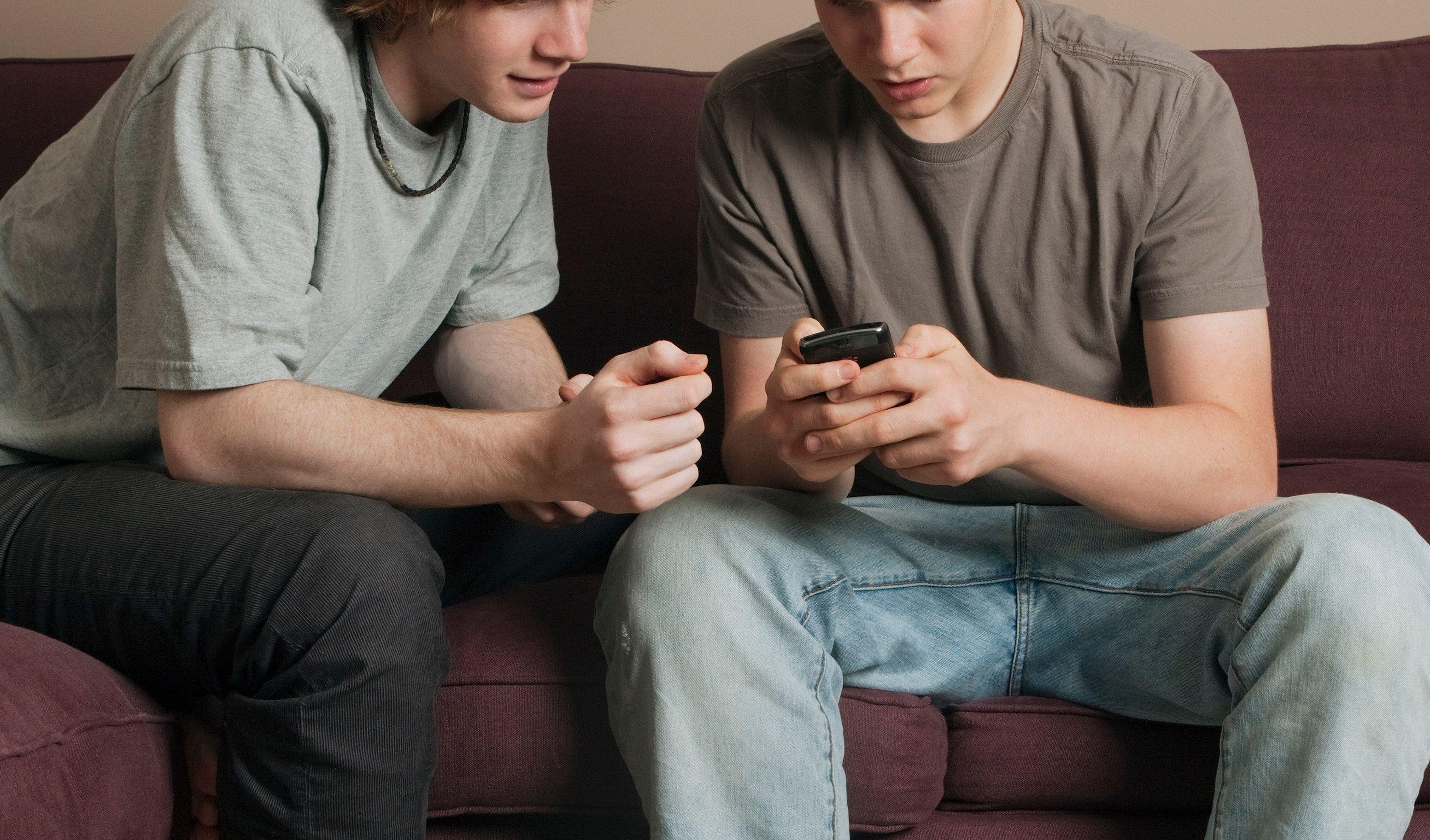 To gutter som ser på en telefon sammen.