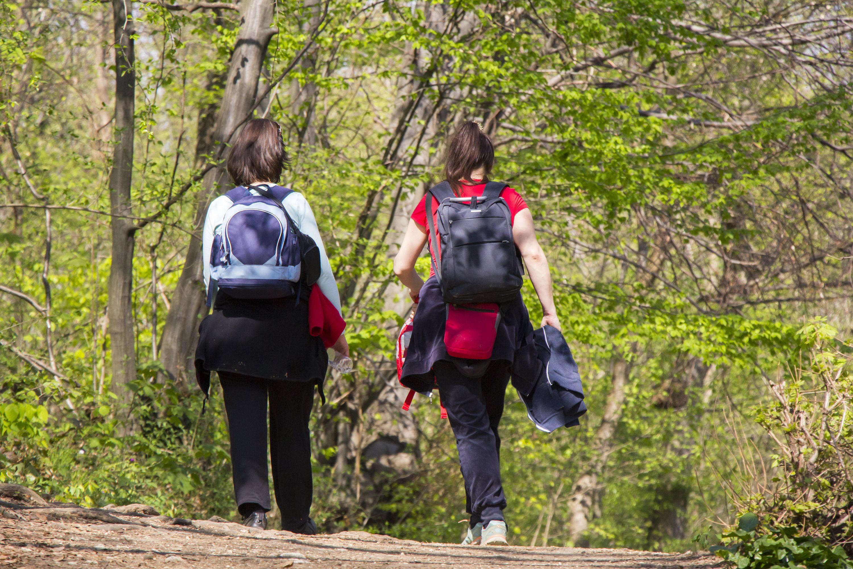 To jenter som går ute i naturen med hver sin ryggsekk.