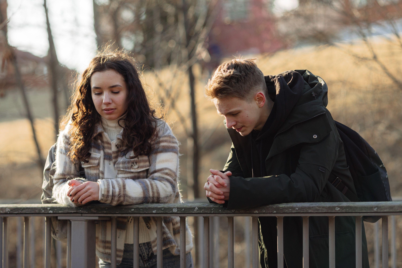 Jente og gutt i midten av tenårene i samtale mens de lener seg på et gjerde