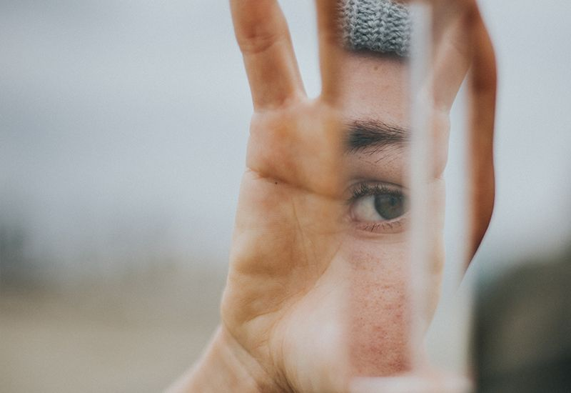 Noen holder en speilbit i hånda, og man kan se øyet til en person i speilet.