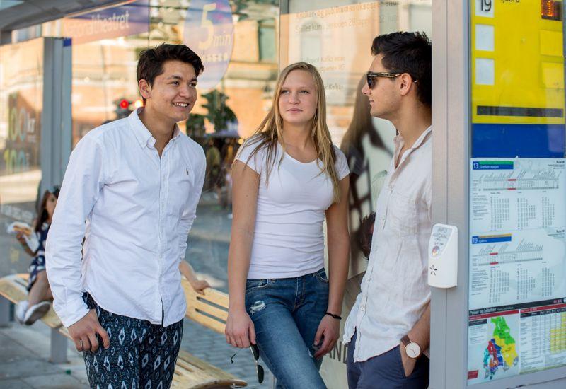 To gutter og en jente venter på bussen (foto: Tine Poppe / bufdir.no)