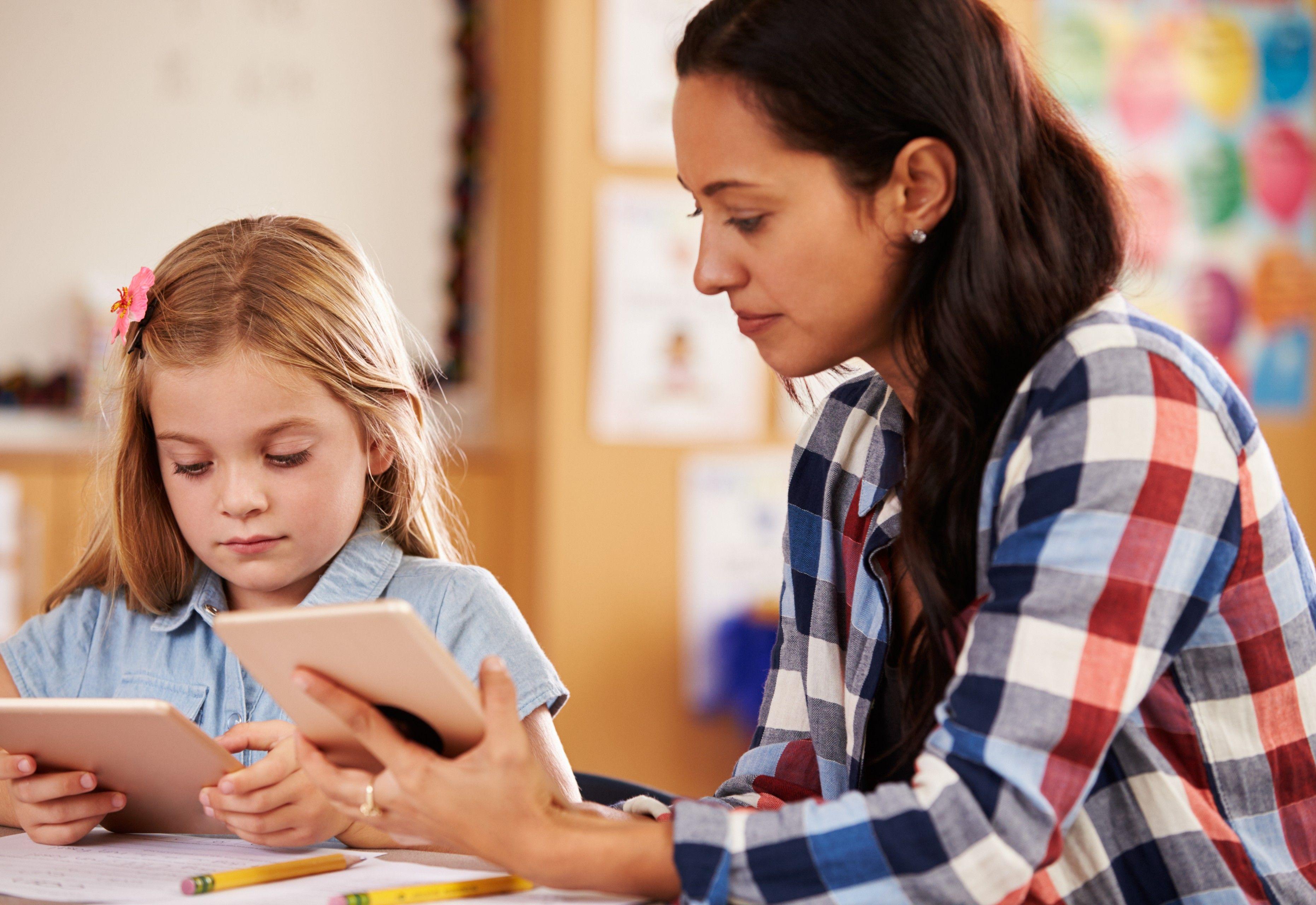 Lærer og jente som sitter med hvert sitt nettbrett.
