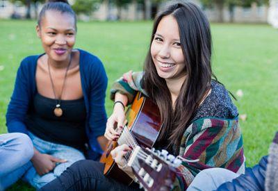 Venner spiller gitar i en park sammen (colourbox.com)