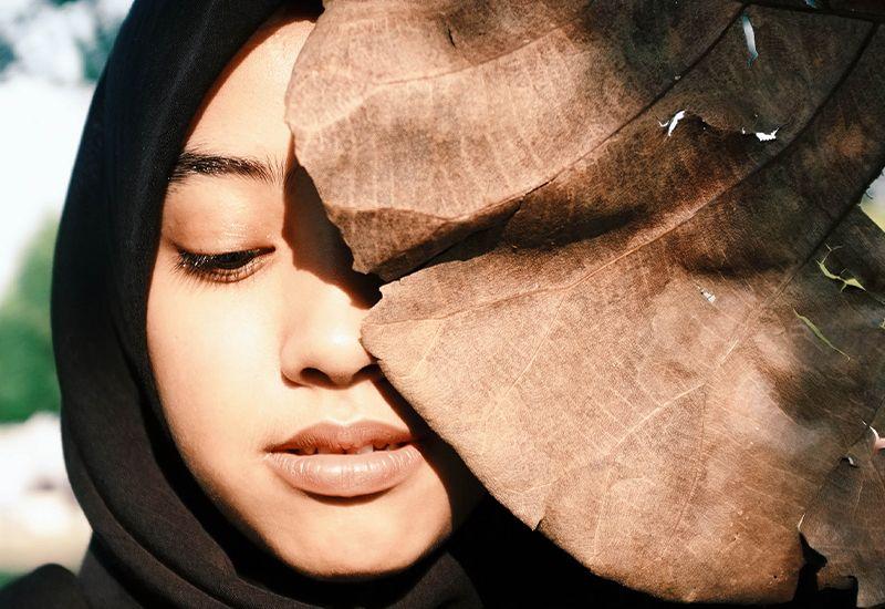 Jente med hijab som har ansiktet delvis gjemt bak et blad.