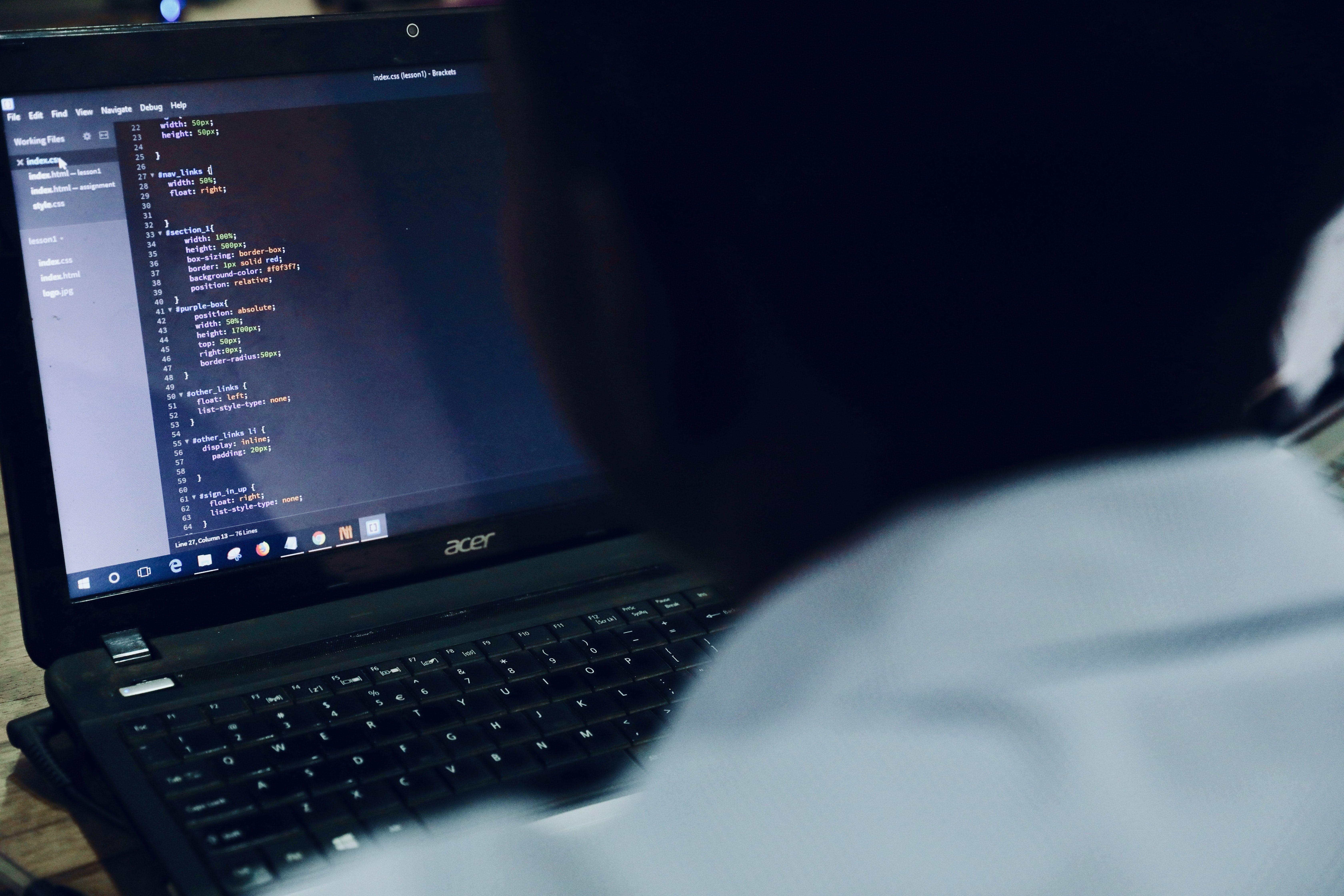 Gutt som ser på en dataskjerm med kode på.