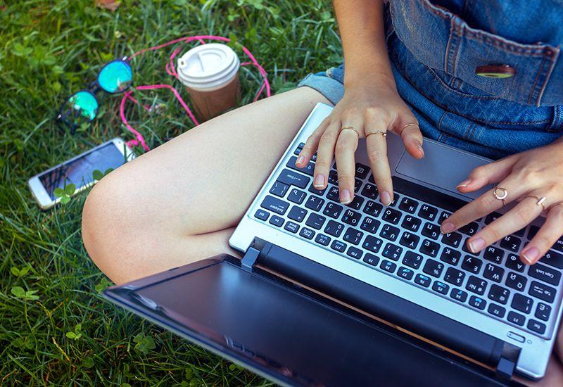 Jente sitter i gresset med en pc (colourbox.com)