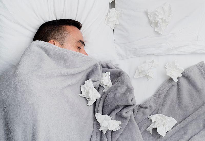 Gutt i senga med masse tørkepapir rundt seg.