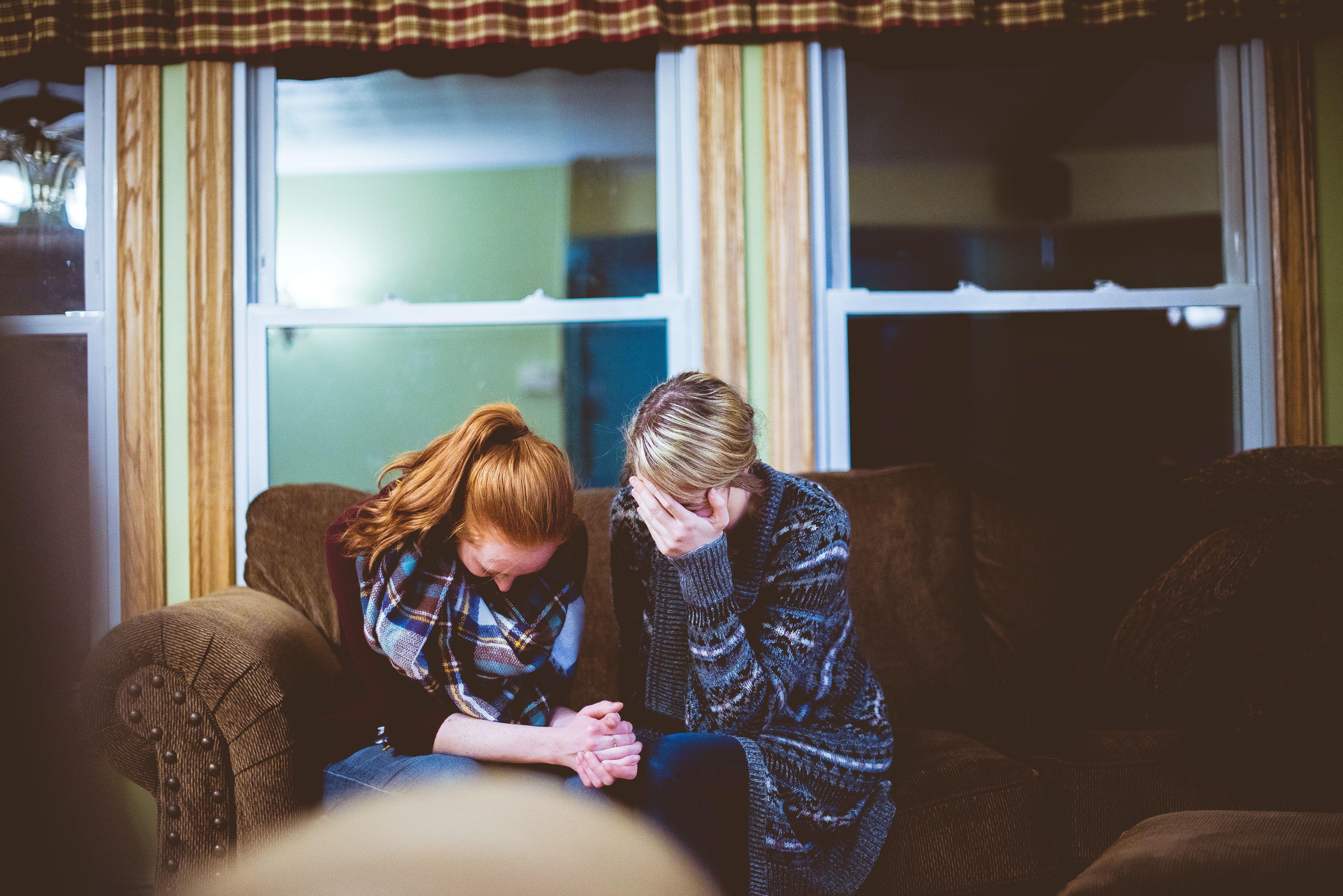 Mor og datter som sitter i en sofa og gråter.