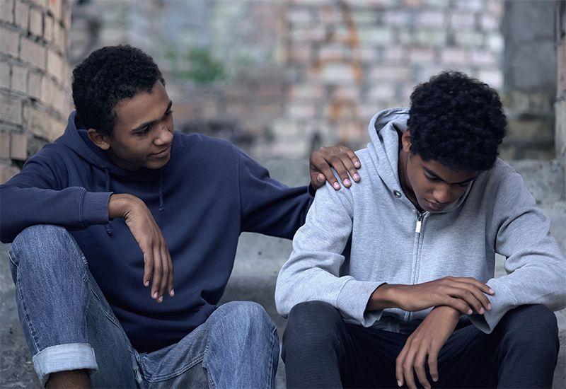 To gutter som snakker, den ene har hånden på skuldra til den andre.