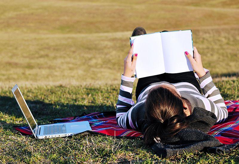 Jente ligger i parken og studerer (colourbox.com)