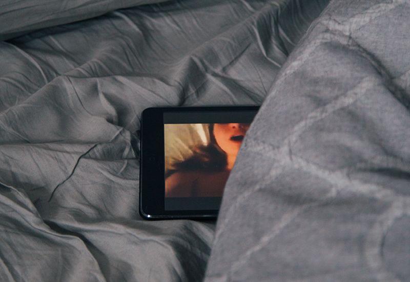 Mobiltelefon i senga (Foto: Charles Deluvio på Unsplash.com)