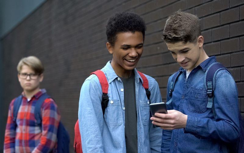 To gutter ser på en telefon og ler. En annen gutt står i bakgrunnen og ser lei seg ut. Foto: Colourbox