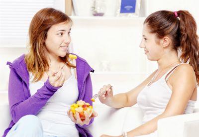 To tenåringsjenter sitter med en skål med frukt foran seg og spiser. (www.colourbox.com)