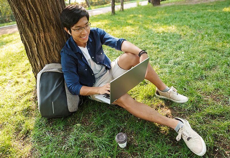 Gutt sjekker laptopen sin i en park (colourbox.com)