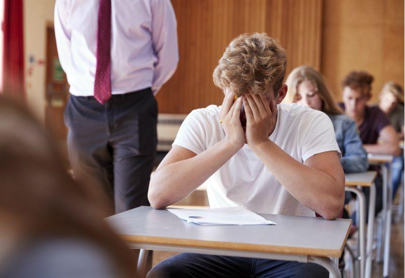 Gutt sitter med hodet i hendene og fortviler over eksamen (Foto: Colourbox.com)