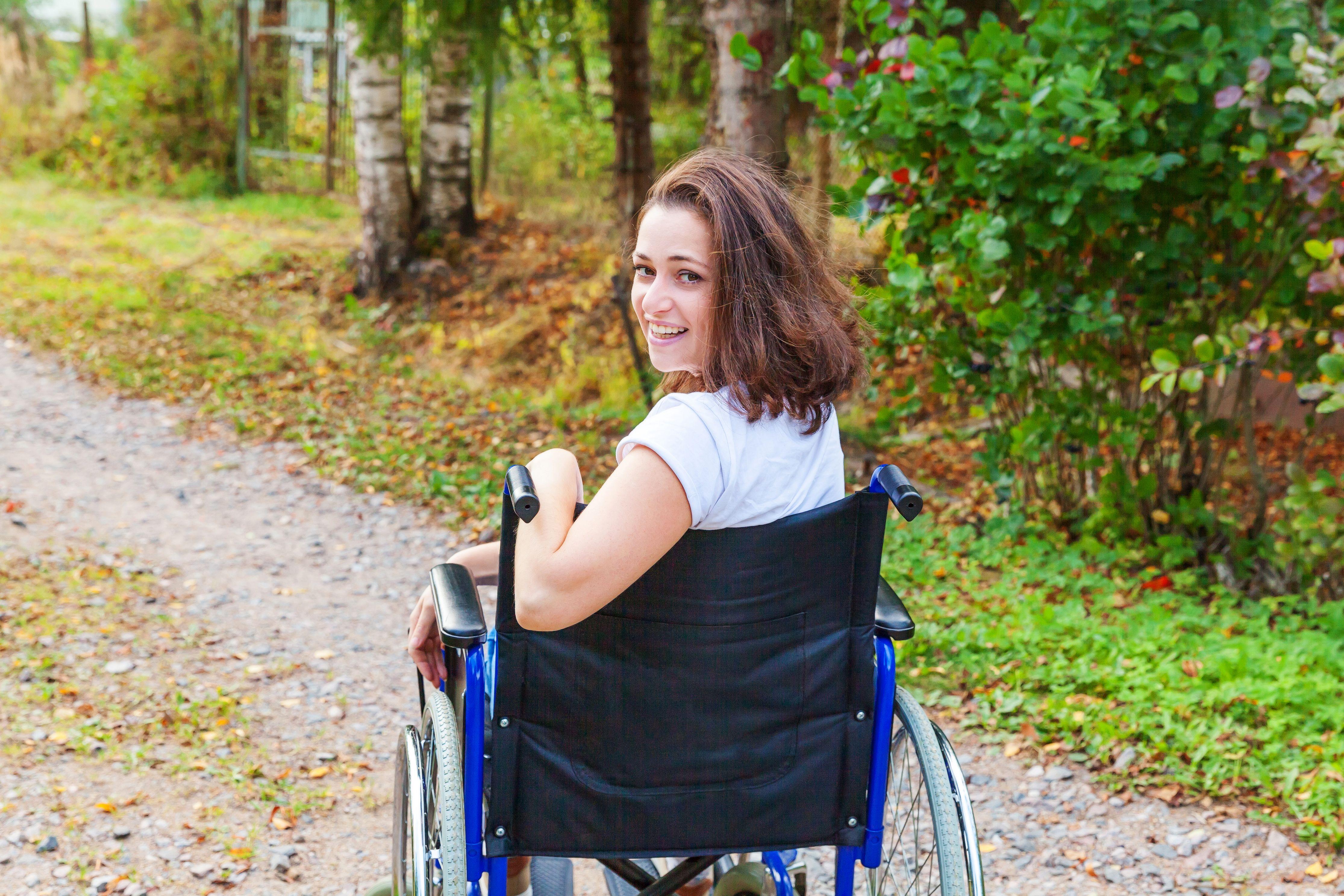 Jente som sitter i rullestol og smiler.