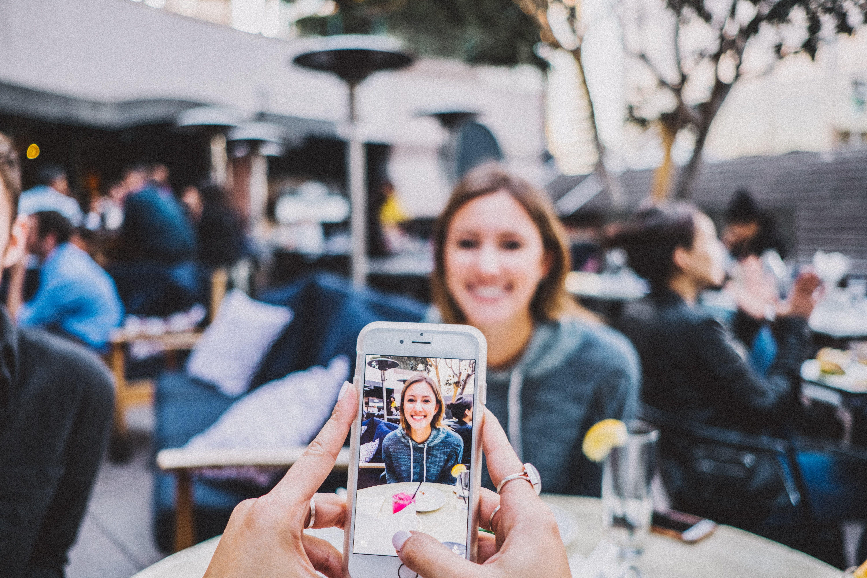 Jente som tar bilde av en annen jente med mobilen sin.