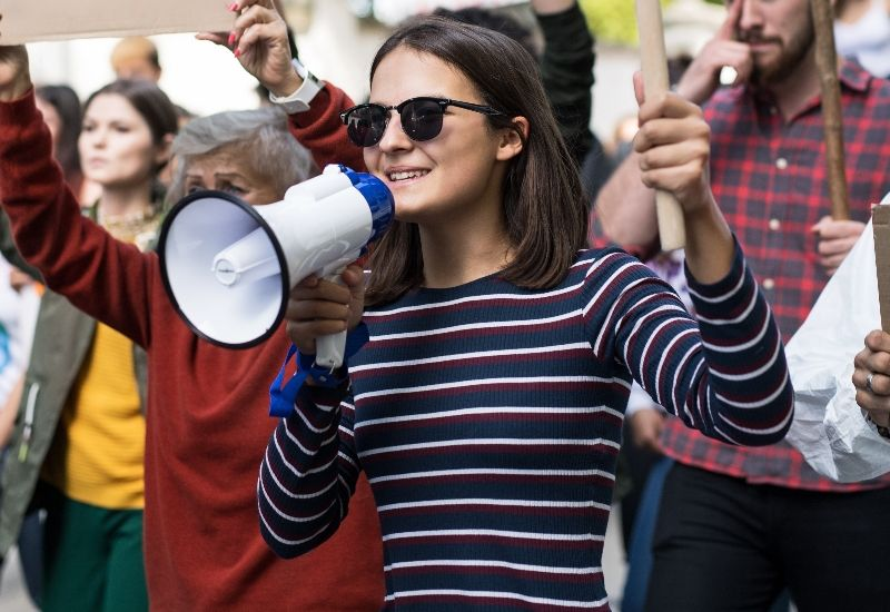 Jente som holder megafon og plakat. Foto: Colourbox.