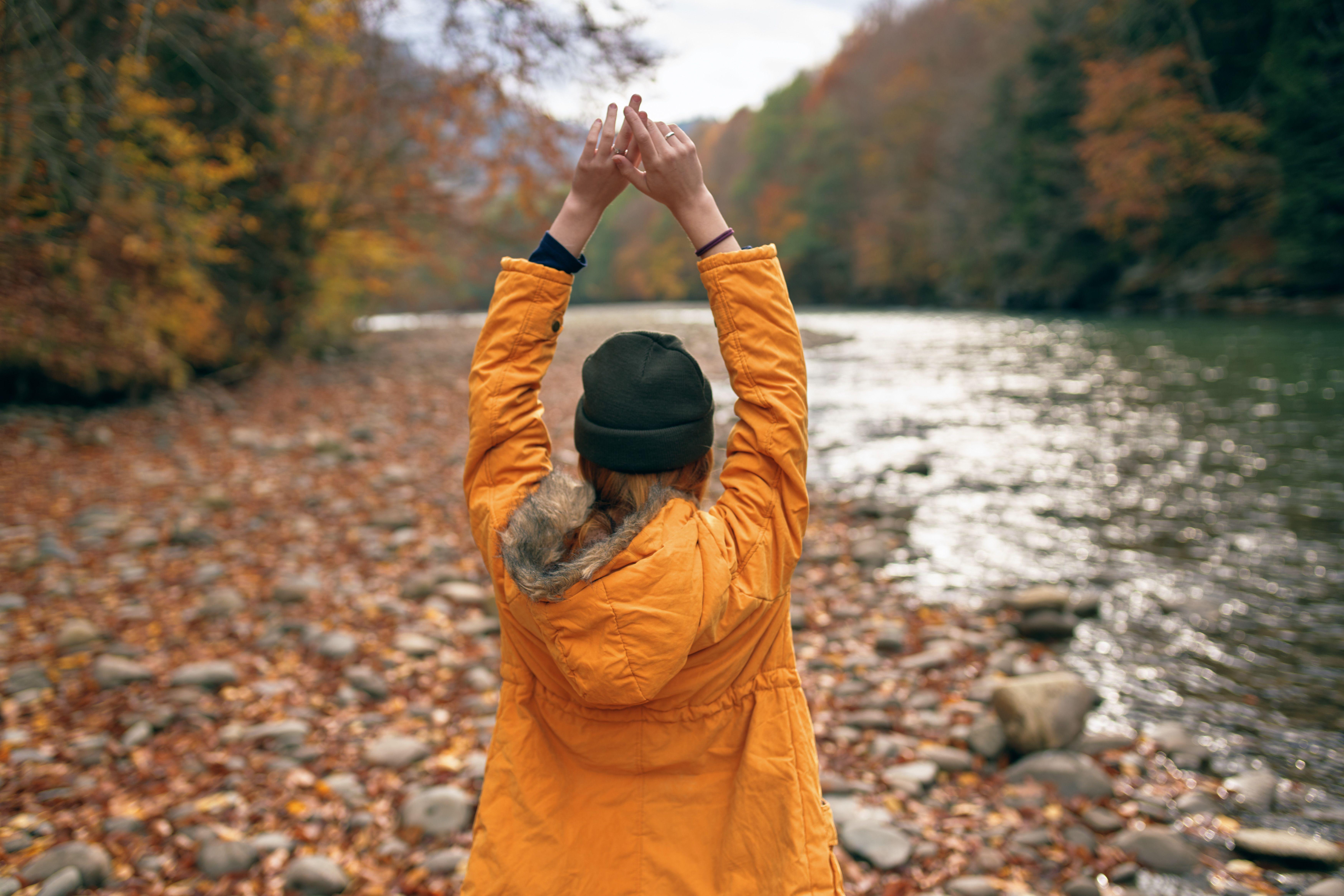 Jente som er ute i naturen og holder hendene over hodet.