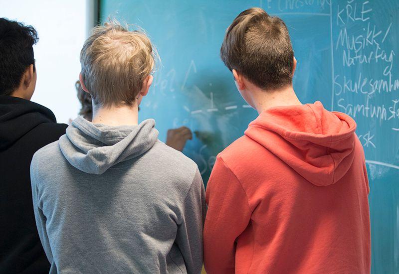 Elever står foran tavla i klasserommet (colourbox.com)