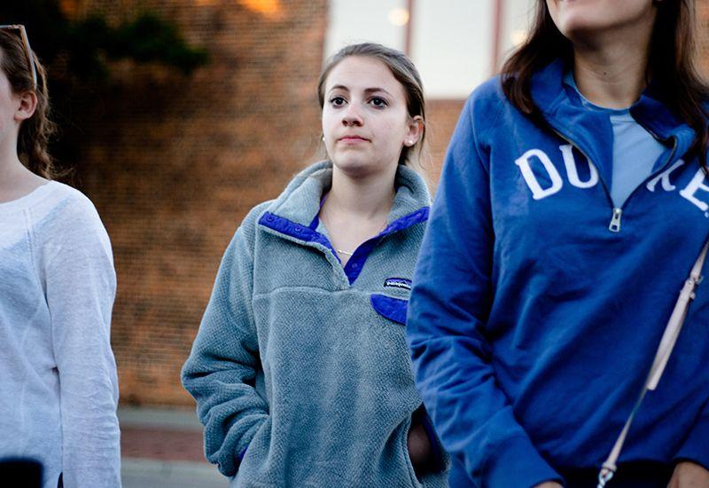 Jente som står bak to andre jenter. Foto: Unsplash.