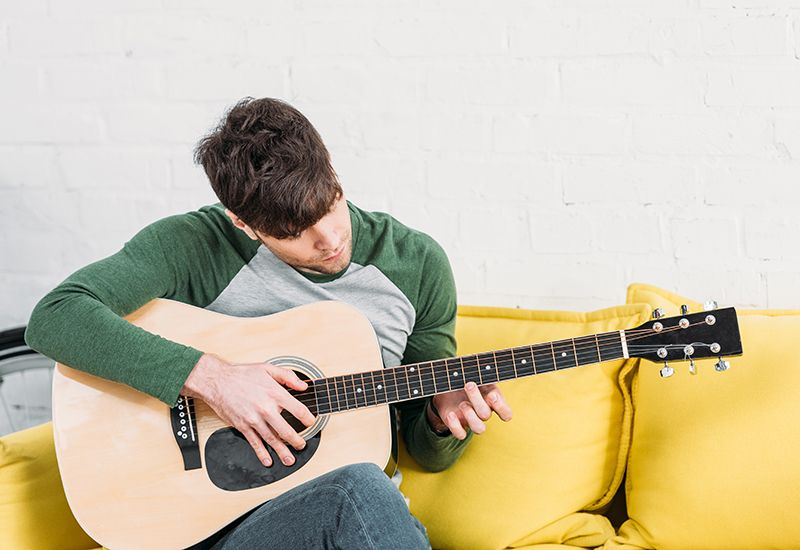 Gutt sitter i sofaen og spiller gitar (www.colourbox.com)