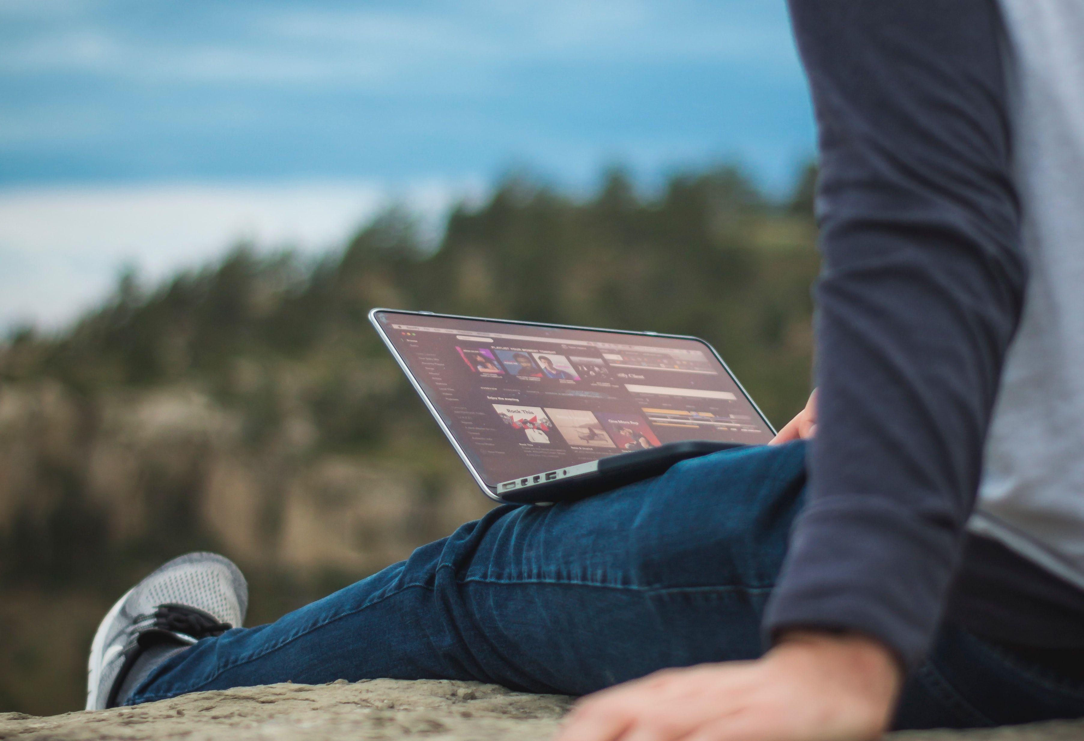Gutt som sitter utendørs med en datamaskin i fanget.