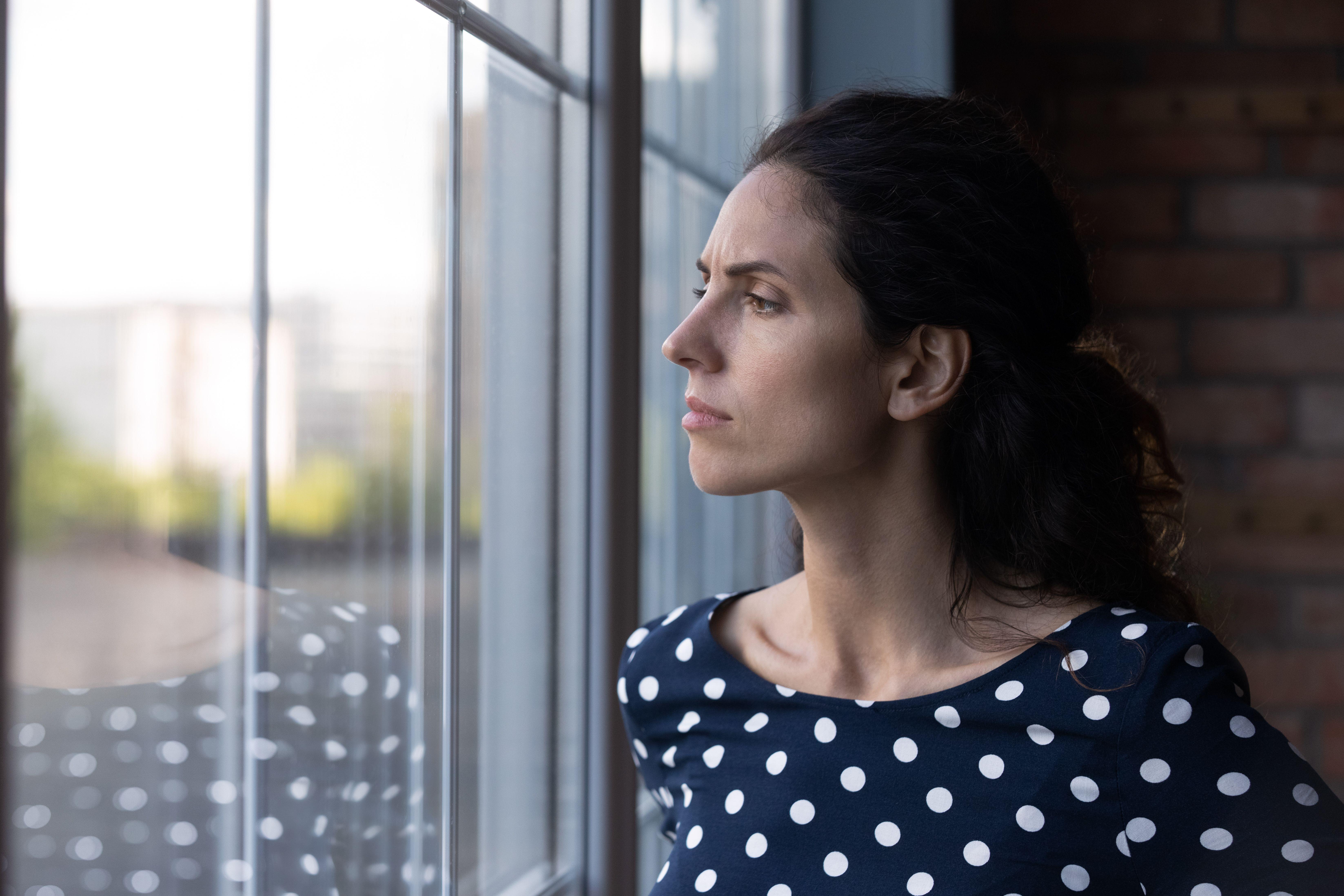 Kvinne som ser bekymringsfult ut vinduet.