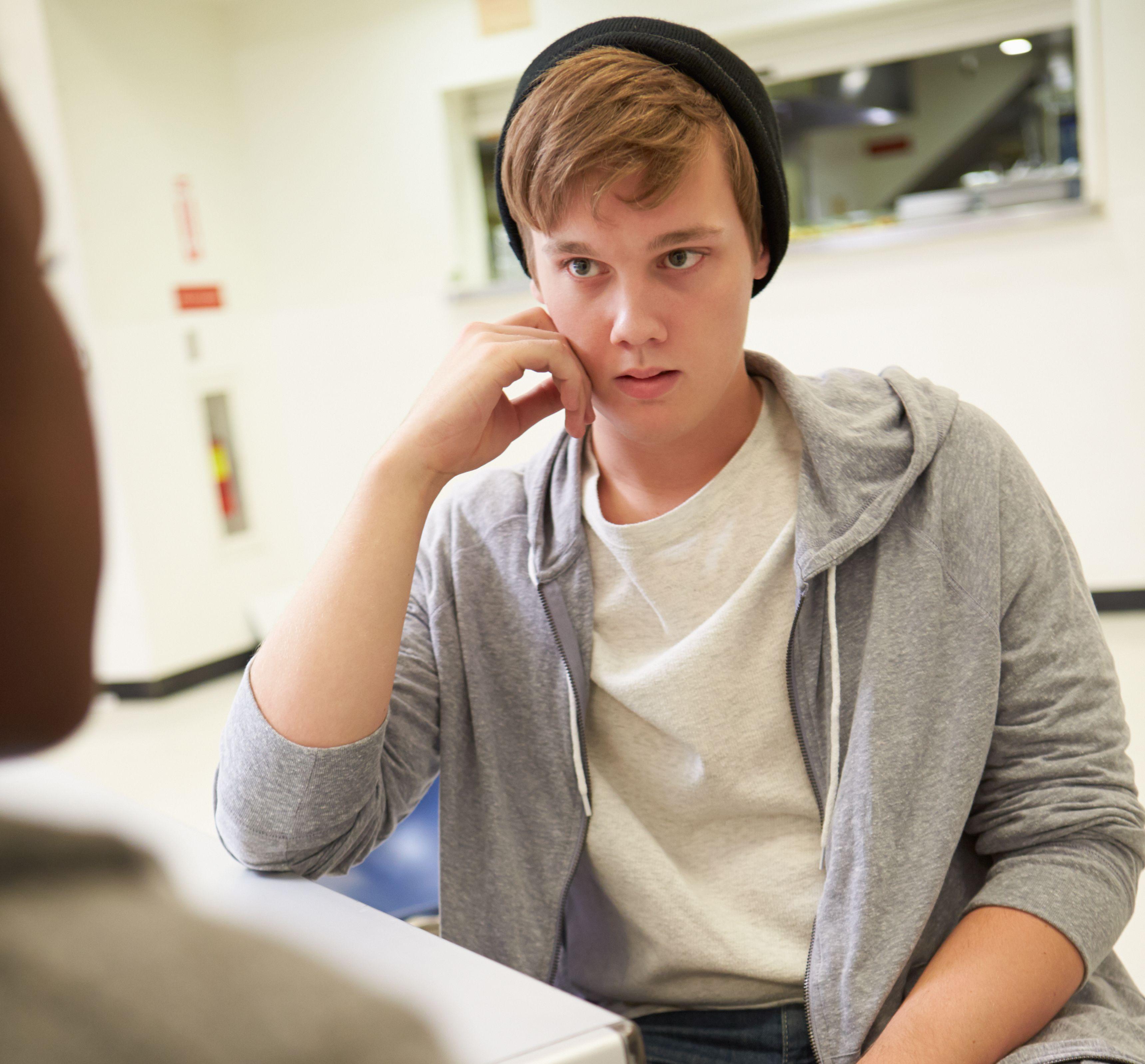Gutt som snakker med en person på en helsestasjon.