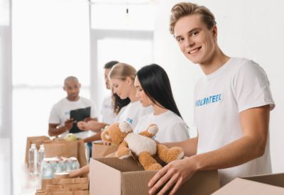 Frivillig ungdom står på rekke ved et bord med bamser, matvarer og drikke. (www.colourbox.com)