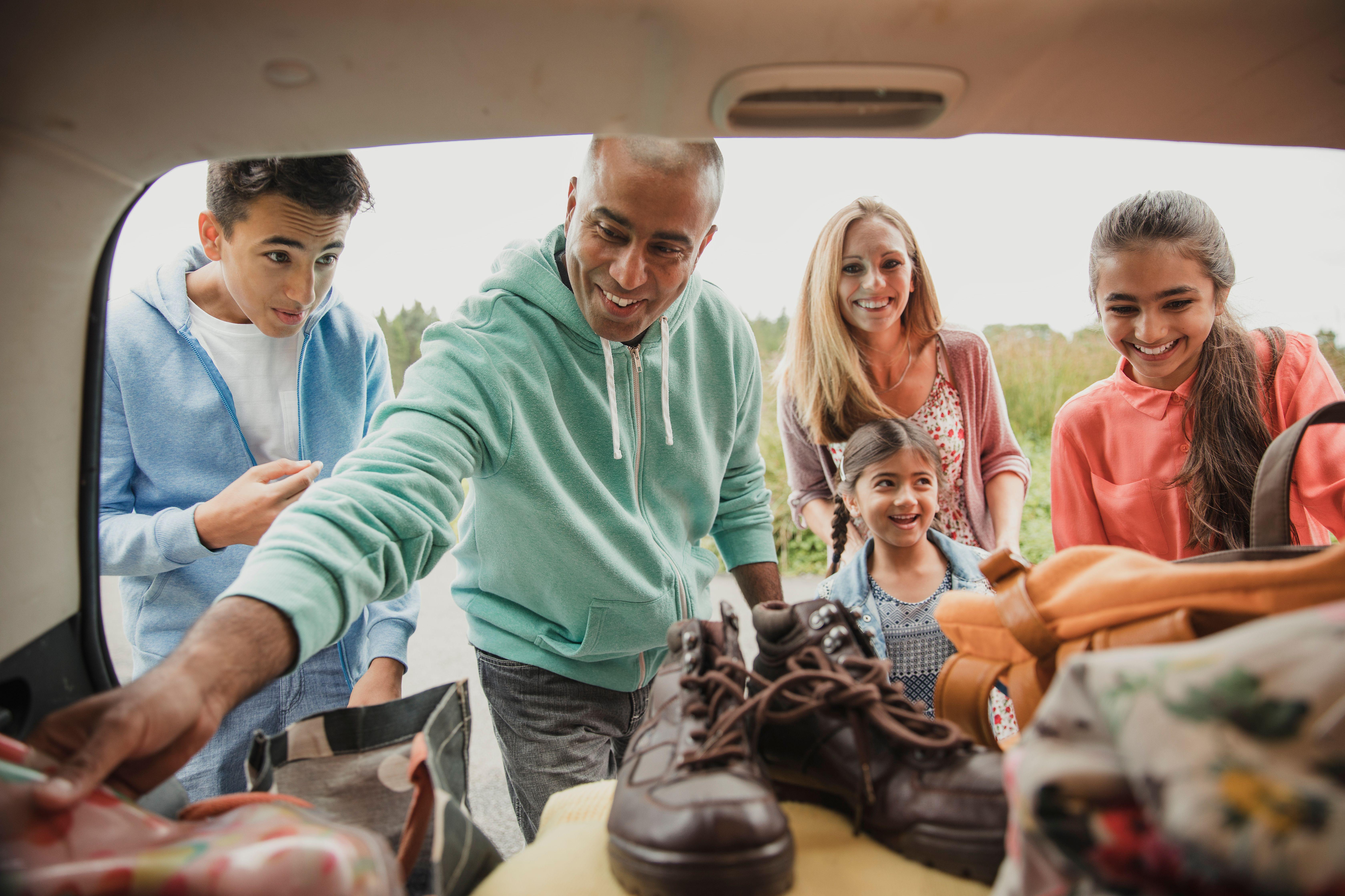 familie som gjør seg klar til å dra på bilferie.