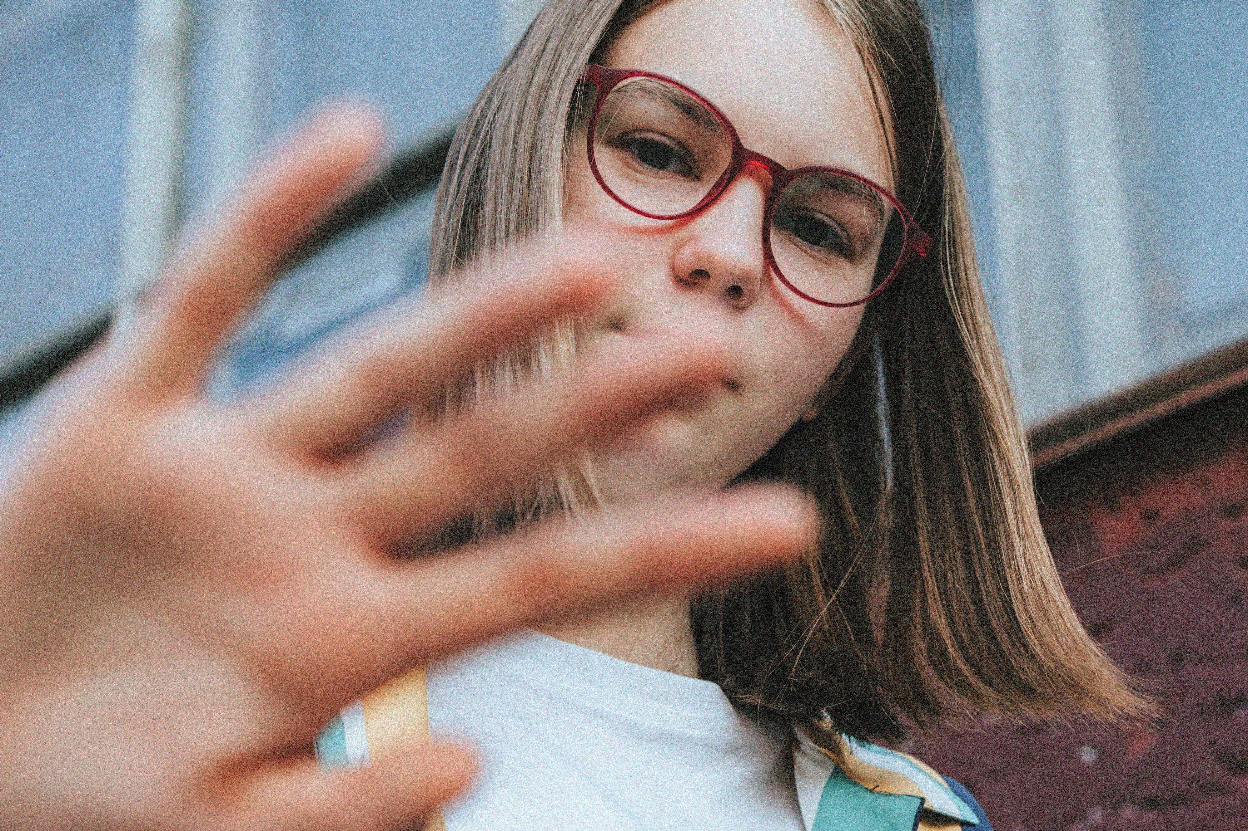 Jente i begynnelsen av tenårene ser ned mot kameraet og holder hånden opp for å hindre at fotografen kommer nærmere.