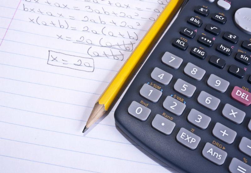 En matteprøve ligger på bordet sammen med en blyant og en kalkulator