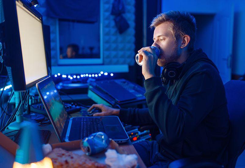 Gutt sitter foran PCen og drikker energidrikk (colourbox.com)