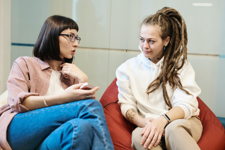Tenåringsjente med dreads i samtale med en voksen kvinne.