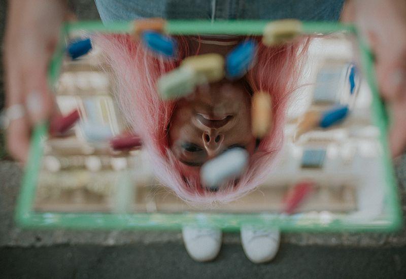 Jente som ser ned på et speil med piller på.