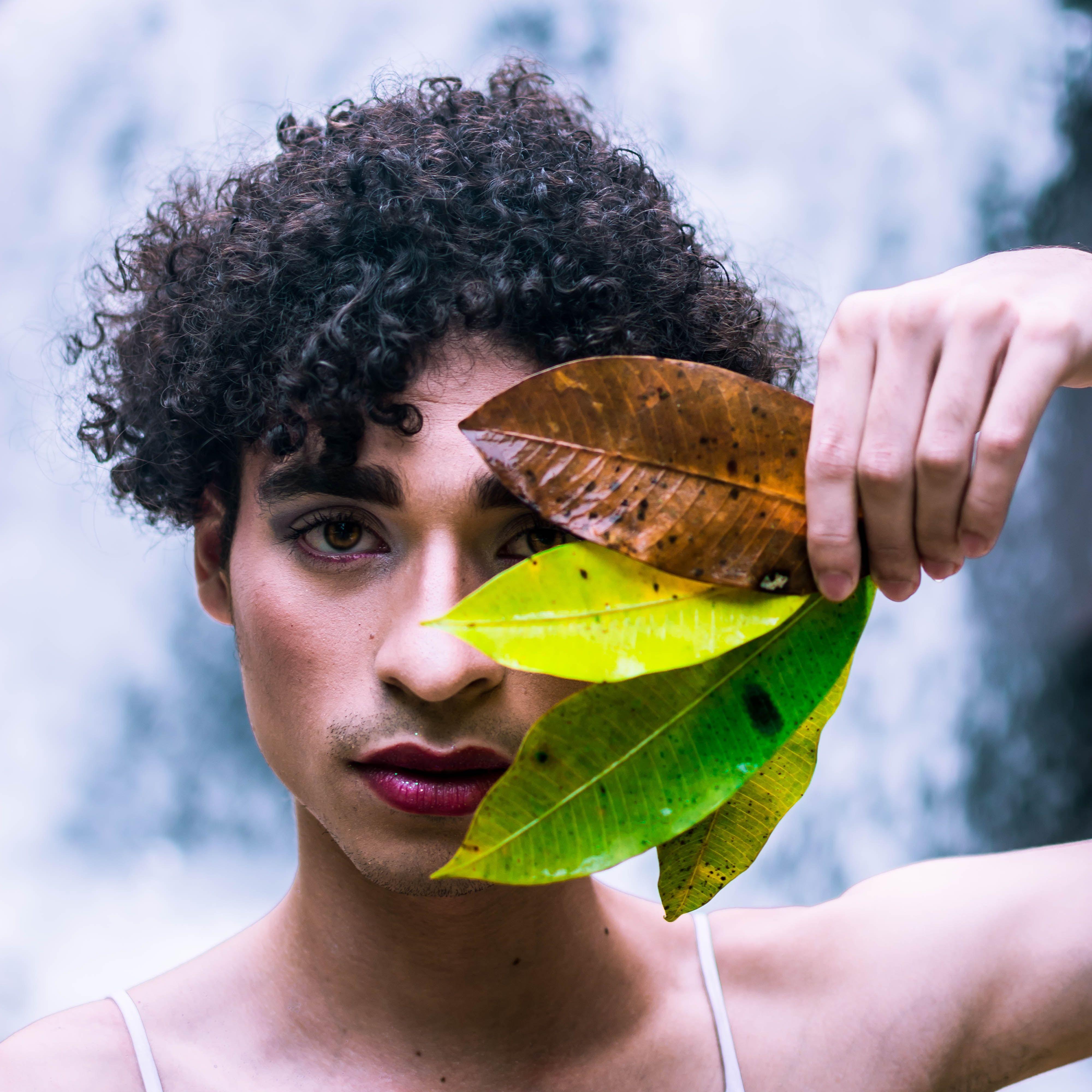 Gutt med sminke som holder noen blader foran ansiktet.