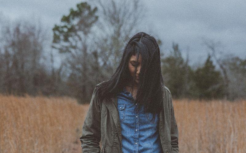 Trist jente med blikket vendt nedover. Foto: Unsplash / Chad Madden