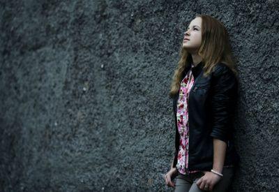 Jente står inntil veggen og tenker (colourbox.com)