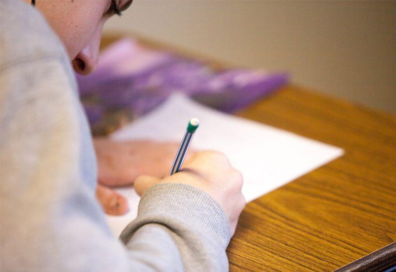Gutt som skriver på et ark. Ser konsentrert ut.