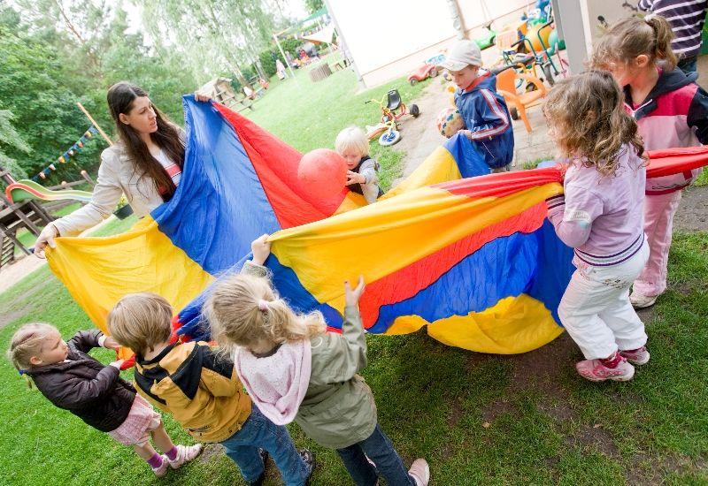 Barnehagelærer og barn som leker utendørs.