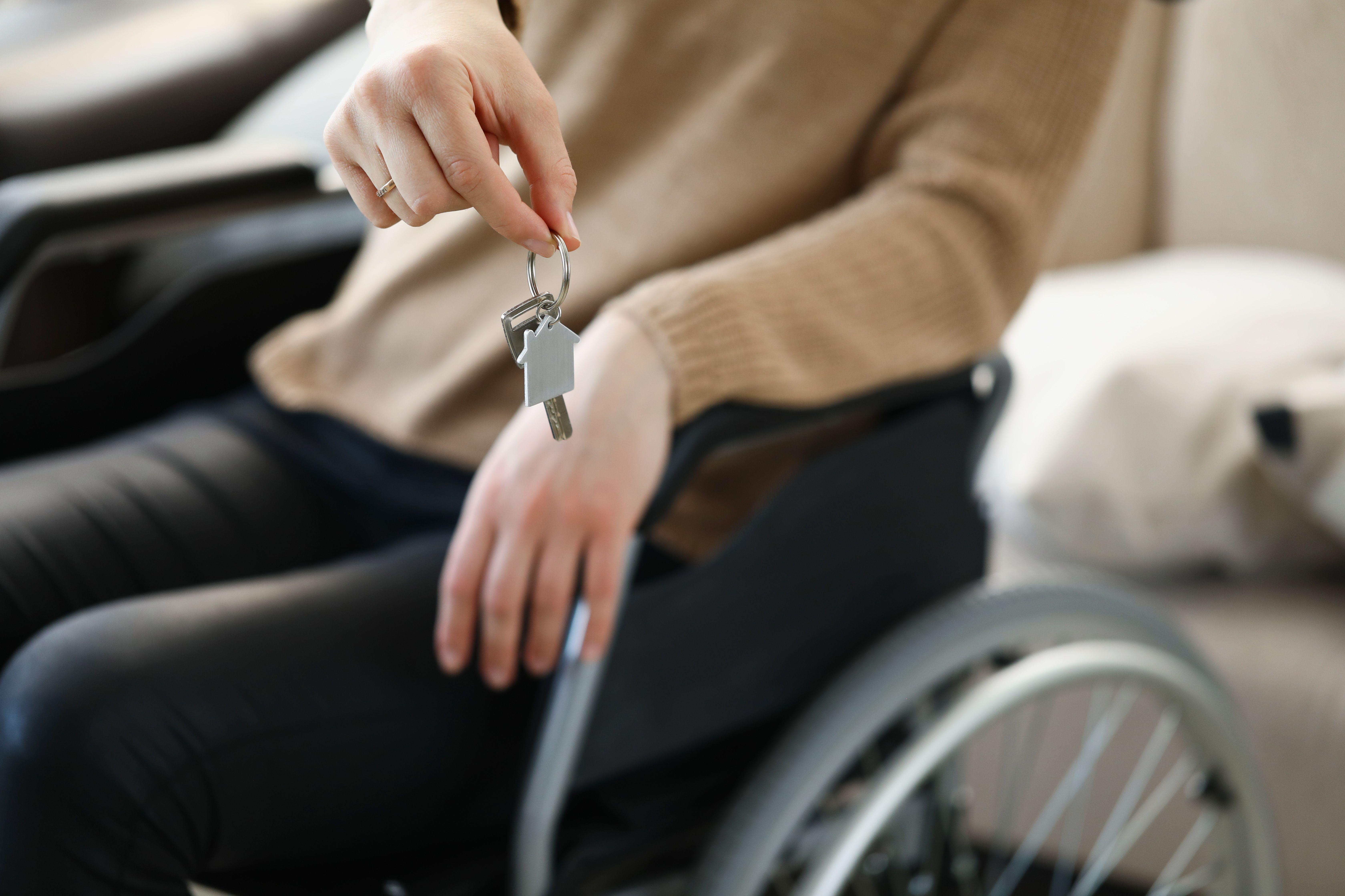 Jente i rullestol som holder et nøkkelknippe.