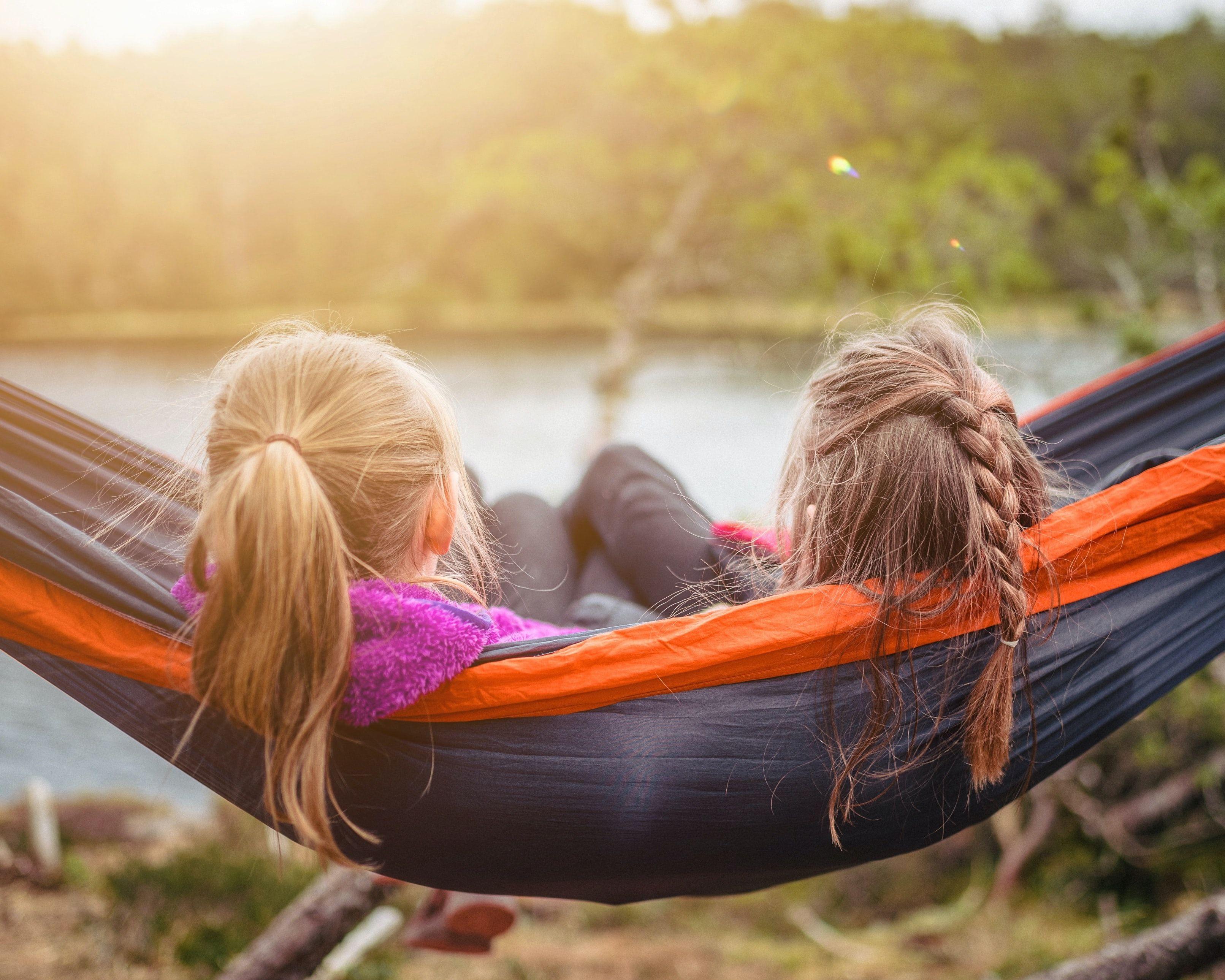 To jenter som sitter sammen i en hengekøye.