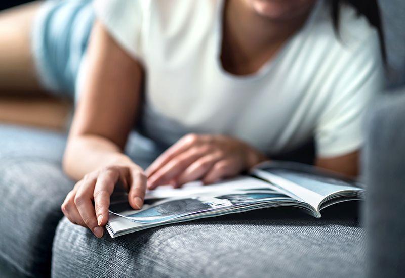 Jente leser magasin på sofaen (colourbox.com)