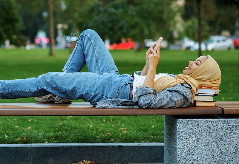 Jente som ligger på en benk og sjekker mobilen.