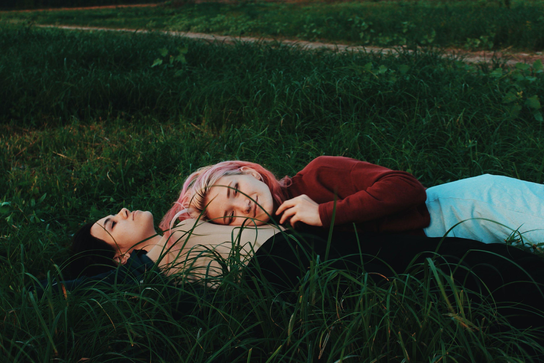 To jenter som ligger i gresset.