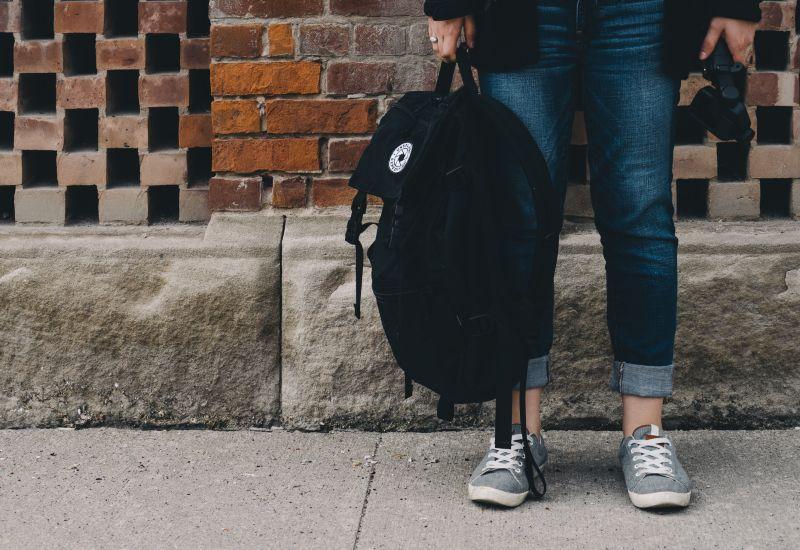 Jente står på gata med en sekk i hånda.