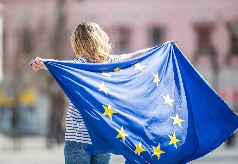 Jente som holder EU-flagg. Foto: Unsplash.
