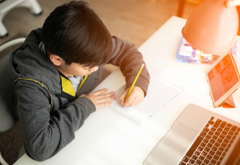 Gutt sitter på pult foran notisblokk og pc (foto: colourbox.com)